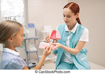 Girl listening to dentist showing her model of teeth