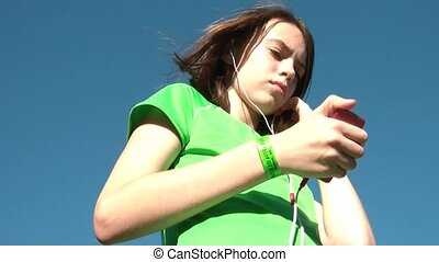 Girl Listening to Music from MP3 Player - Girl listening to...