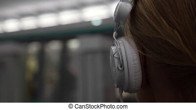 Girl listening to music in metro - Close-up back shot of a...