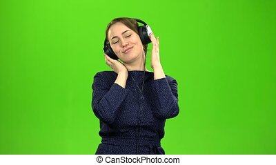 Girl listening to music on headphones. Green screen