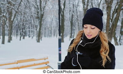 Girl listening to music on headphones, is in the winter park