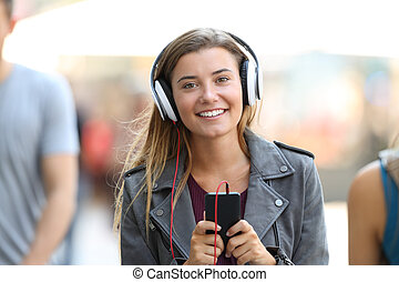 Girl listening to music on phone and looking at you