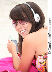 Girl listening to music on the beach