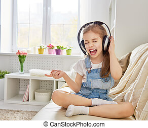 girl listening to music - little girl with headphones at...