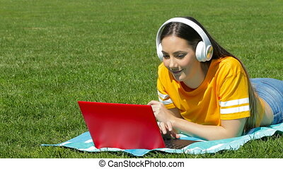Girl listening to music with a laptop and headphones - Happy...