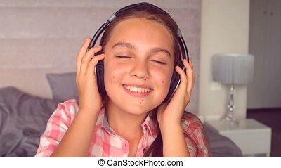 Girl listening to music with headphones in slow motion at...