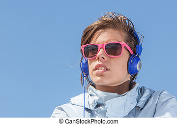 Girl listening to music with pink sun glasses