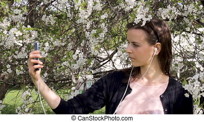 Girl listening to the music and taking a selfie in blooming garden