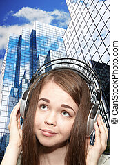 Girl listening to the music. The skyscrapers