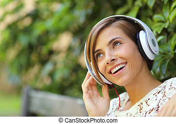 Girl listening to the music with headphones in a park