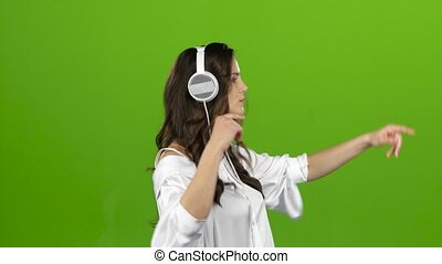 Girl listens through the headphones music and whirl around her. Green screen