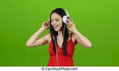 Girl listens to cheerful and energetic music through headphones. Green screen