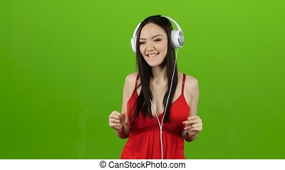 Girl listens to cheerful music through headphones and dances. Green screen