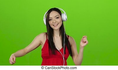 Girl listens to cheerful music through headphones and dances. Green screen. Slow motion