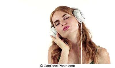 Girl listens to her favorite music through headphones. White...