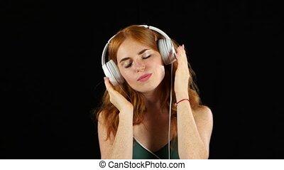 Girl listens to her favorite music through headphones. Black...