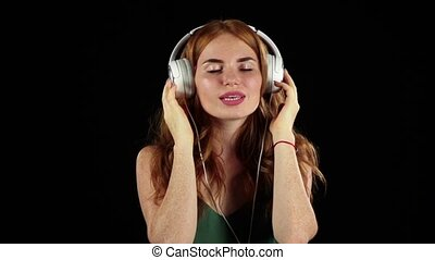 Girl listens to her favorite music through headphones. Black background. Slow motion