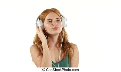 Girl listens to her favorite music through headphones. White...