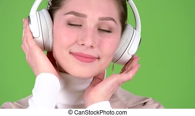Girl listens to melodious songs in the headphones. Green screen. Close up