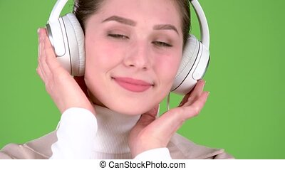 Girl listens to melodious songs in the headphones. Green screen. Close up . Slow motion