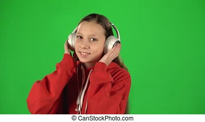 Girl listens to music and moving in large white headphones on green background