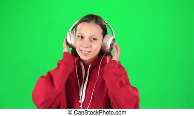 Girl listens to music and moving in large white headphones on green background. Slow motion