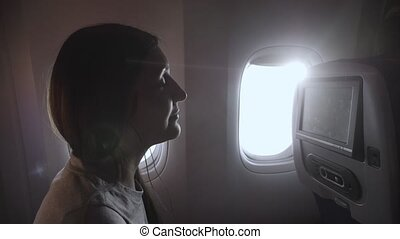girl listens to music in airliner passenger cabin closeup