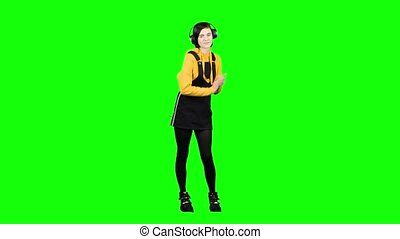 Girl listens to music in headphones and claps her hands. Green screen