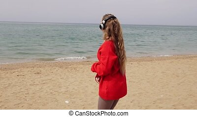 girl listens to music in large headphones on the beach by the sea
