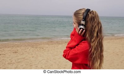 girl listens to music in large headphones on the beach by...