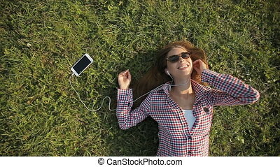 Girl Listens to Music on Grass