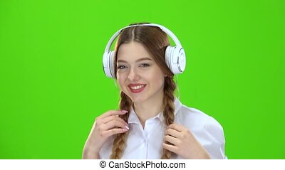 Girl listens to music on headphones . Green screen