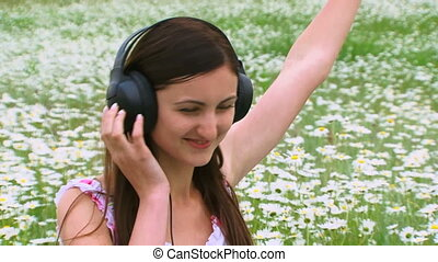 Girl listens to music on the field