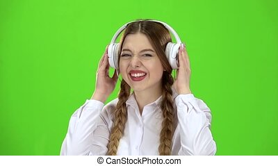 Girl listens to music through headphones. Green screen. Slow motion
