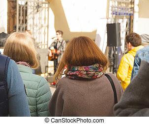 Girl listens to street musicians