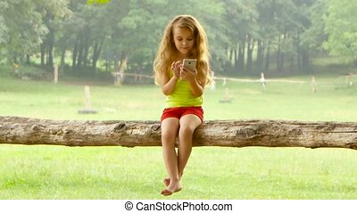 Girl little with long hair is playing on smartphone sitting in a tree on beautiful summer day