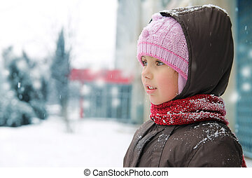 Girl looking aside in winter cloths while snowing
