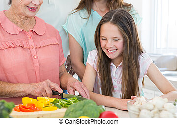 Girl looking at grandmother cutting vegetables