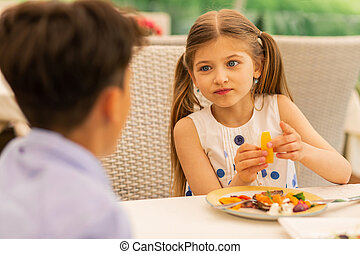 Girl looking at her older brother while having breakfast