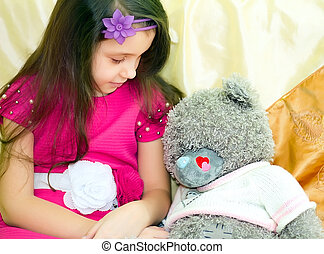 Girl looking at teddy bear
