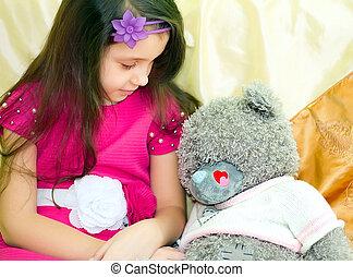Girl looking at teddy bear