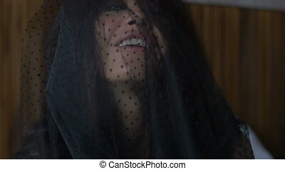 girl looking at the camera laughing and hides her face behind a cloth