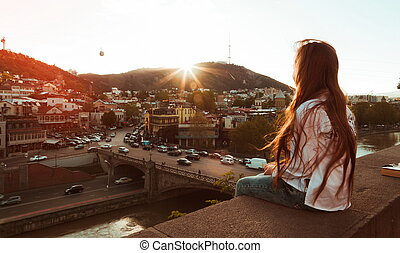 girl looking at the city at sunset