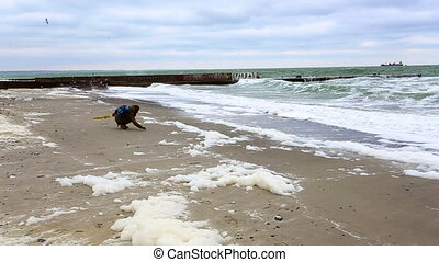 girl looking at the stormy sea standing on a sandy beach