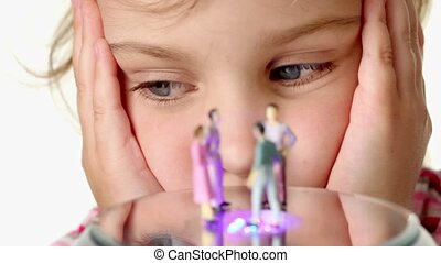 Girl looking at toy podium, on its stand toy figurines