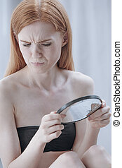 Girl looking into broken mirror - Red hair girl looking into...