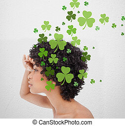 Girl looking into distance with shamrocks on white wall...