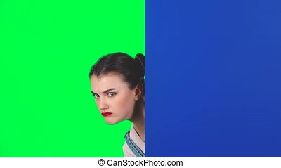 Girl looking out from behind blue blank placard and calls to herself pointing finge on green screen at studio, slow motion. Girl with two hair-buns and red lips. Copy space. Ready for your text or product