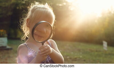 Girl looking through a magnifier at sunset