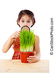 Girl looking through a magnifier - Surprised girl looking at...